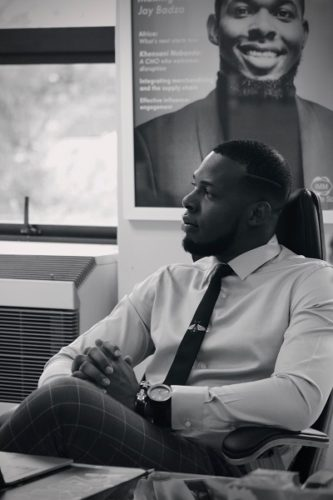 Jay Badza seated with framed magazine cover on wall
