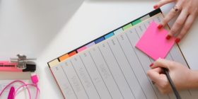 person-holding-pencil-and-sticky-note by Marten Bjork courtesy of unsplash